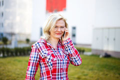 Blonde businesswoman in flannel shirt calling Royalty Free Stock Image