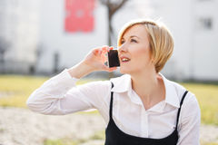 Blonde businesswoman in formal wear calling outdoor Royalty Free Stock Photos