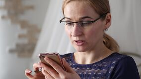 Blonde businesswoman in glasses checking something on smartphone. 4K. Blonde businesswoman in glasses checking something on smartphone stock video footage