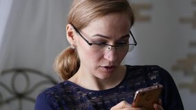 Blonde businesswoman in glasses checking something on smartphone. slow motion. Blonde businesswoman in glasses checking something on smartphone stock video footage