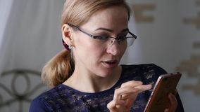Blonde businesswoman in glasses checking something on smartphone. slow motion. Blonde businesswoman in glasses checking something on smartphone stock footage
