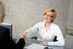 Blonde businesswoman in glasses handshake Stock Photos