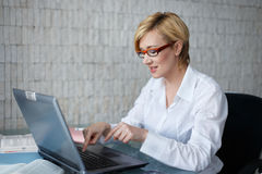 Blonde businesswoman in glasses typing Royalty Free Stock Image