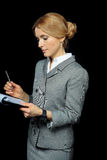 Blonde businesswoman holding folder with papers and pen on black Stock Photography