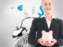 Blonde businesswoman holding piggy bank Royalty Free Stock Photos