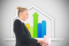 Blonde businesswoman holding piggy bank Stock Image
