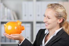 Blonde Businesswoman Holding A Piggy Bank Stock Photo