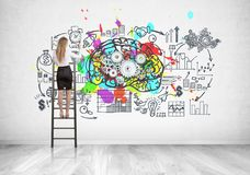 Blonde businesswoman on ladder, cog brain. Rear view of a blonde businesswoman standing on a ladder and drawing a business plan and a brain with gears sketch on Stock Photography