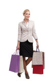 Blonde businesswoman in a light beige suit holding shopping bags Stock Photo