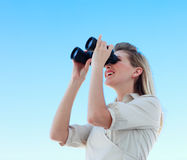 Blonde businesswoman looking through binoculars Stock Images