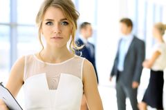 Blonde businesswoman looking at camera. While standing straight in office Royalty Free Stock Photography