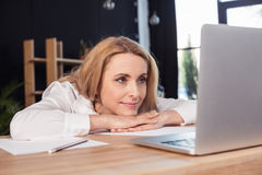 Blonde businesswoman looking at laptop while sitting at wooden table Royalty Free Stock Images