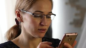 Blonde businesswoman making a video communication on smartphone with friends. slow motion. Blonde businesswoman making a video communication on smartphone with stock footage