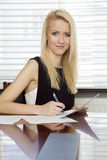 Blonde businesswoman in office. Business concept - portrait of a beauty young adult attractive pretty blonde businesswoman in office Royalty Free Stock Photos