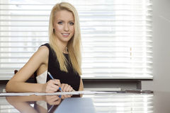 Blonde businesswoman in office. Business concept - portrait of a beauty young adult attractive pretty blonde businesswoman in office Royalty Free Stock Image