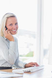 Blonde businesswoman on the phone smiling at camera Stock Photos