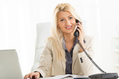 Blonde Businesswoman Phoning In The Office. A young blond businesswoman phoning in office, sitting at an office desk in front of laptop, with a smile on her face Stock Photography