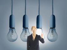 Blonde businesswoman pointing at huge light bulb Stock Image