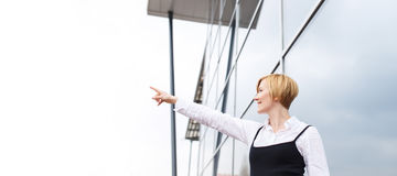Blonde businesswoman pointing to sky at financial center Stock Images