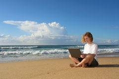 Blonde businesswoman sits with notebook on beach Royalty Free Stock Images