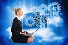 Blonde businesswoman sitting using laptop with cogs and wheels Stock Photo