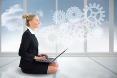 Blonde businesswoman sitting using laptop with cogs and wheels Royalty Free Stock Images