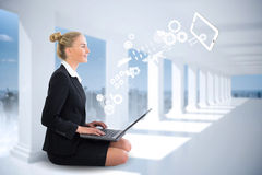 Blonde businesswoman sitting using laptop with cogs and wheels Stock Photography