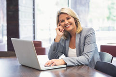 Blonde businesswoman smiling using laptop Stock Images