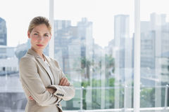 Blonde businesswoman standing with arms crossed Stock Photos