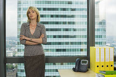 Blonde businesswoman standing beside office window, arms folded, smiling, front view, portrait Stock Photo