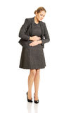Blonde businesswoman with strong stomachache Royalty Free Stock Image