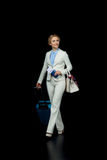 Blonde businesswoman with suitcase in white suit ready to trip on black. Happy blonde businesswoman with suitcase in white suit ready to trip on black Royalty Free Stock Photography
