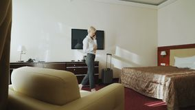 Blonde businesswoman talking on phone then taking her suitcase and leaving hotel room at check-out time. Travel. Blonde young businesswoman talking on phone then stock footage