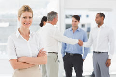 Blonde businesswoman with team behind her smiling at camera Royalty Free Stock Photography