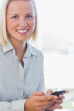Blonde businesswoman texting and smiling Stock Photos