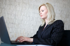 Blonde businesswoman typing on laptop Royalty Free Stock Photography