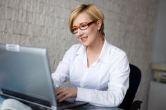 Blonde businesswoman in typing on laptop Stock Images