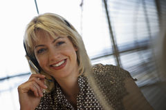 Blonde businesswoman wearing telephone headset, smiling, close-up, portrait (tilt) Stock Image