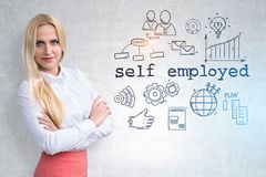 Confident blonde self employed businesswoman. Blonde businesswoman in white shirt and pink skirt standing with crossed arms near a concrete wall with self royalty free stock photography