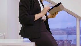 Blonde businesswoman working on tablet, crane down shot on beautiful legs stock video