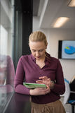 Blonde businesswoman working on tablet at office Stock Photography