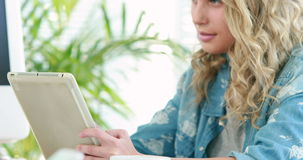 Blonde casual businesswoman using tablet computer. In the office stock footage