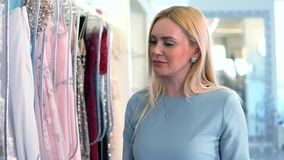 Blonde caucasian female looking at dresses. Shopping in women`s clothing store. stock footage
