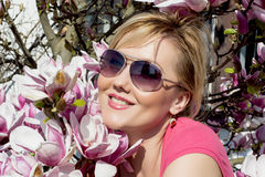 Blonde caucasian woman and blooming magnolia Royalty Free Stock Photography