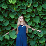 Blonde caucasian woman lost among ivy leaves Stock Photos