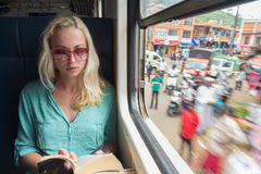 Blonde caucasian woman reading book on train by the window. Royalty Free Stock Photo