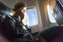 Blonde caucasian woman sneezing while traveling by airplane. stock photography