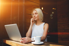 Blonde Caucasian woman talking on cell telephone during work on portable laptop computer Stock Photography