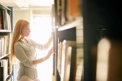 Blonde teacher searching book in the library in school. Blonde caucasian young woman searching book in the old bookstore walking along long rows of bookshelves stock image