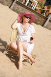 Blonde in a chaise longue on the beach Royalty Free Stock Photography